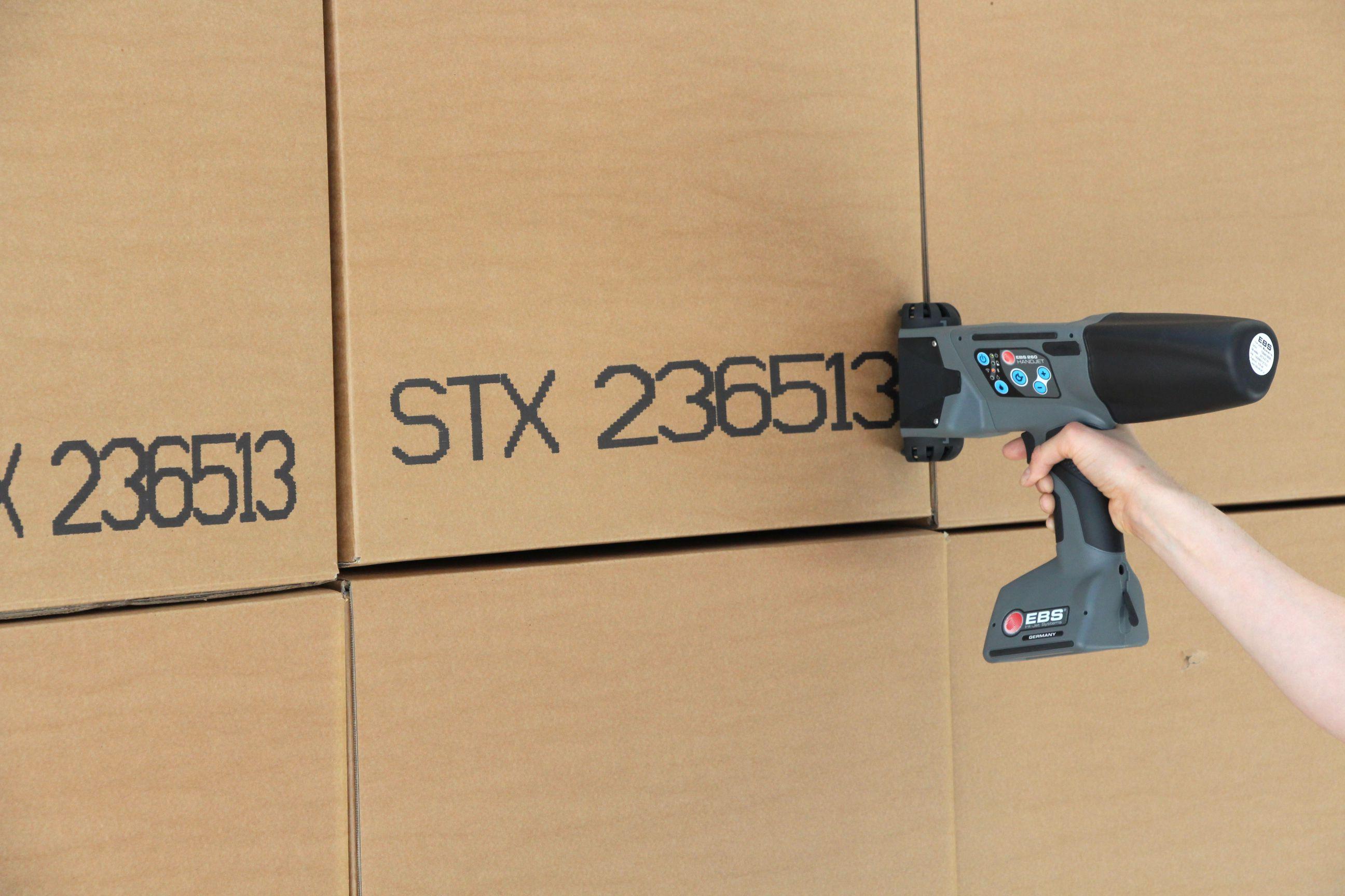 Picture Showing Handheld Inkjet Printer Printing On Cardboard